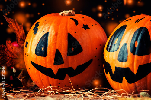Halloween festive composition with smiling pumpkins guards, lantern, straw and fallen leaves on dark wooden background, rustic style, selective focus