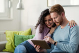 Young couple using digital tablet at home - 229714542