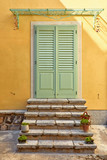 Stone stairs by wooden entrance door in old house of antique - 229715923