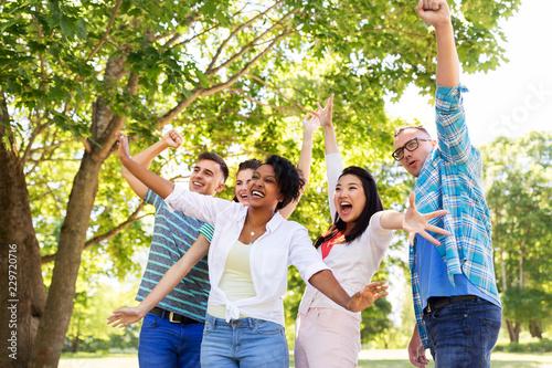 Leinwandbild Motiv people, friendship and international concept - group of happy smiling friends having fun outdoors
