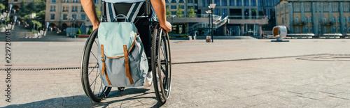 przycięty panoramiczny widok człowieka za pomocą wózka inwalidzkiego z torbą na ulicy