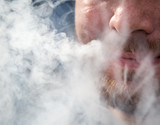 Smoke from the nose of a man from a cigar - 229735329