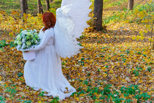 A woman in a white angel costume on a background of the autumn landscape. - 229756347