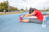 Woman in 40s is stretching before jogging at city park - 229756503