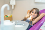Happy smiling baby girl seated on dentist chair in a modern dentist room - 229756588