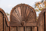 Traditional hand carved symbolic old gate fragment. Bird and sun motifs on the gate. Traditional gate motifs. - 229756707