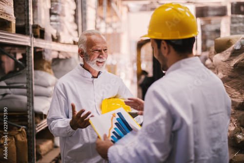 Picture of two male warehouse employees talking about trade success of their storage. Standing in warehouse in white clothes and yellow helmets . One of them is holding paper with histogram on it.