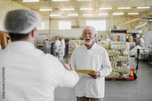 Picture of mature cheerful older man in sterile clothes standing in food factory and being happy about seeing his colleague. Team work and good job concept.