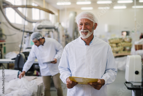Father and son checking products in their food factory. Mature man in sterile clothes standing in front of the camera with smile on his face.Successful business concept.
