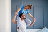Man holding his beautiful blond girlfriend on his shoulders early in the morning while they are in pajamas. - 229770541