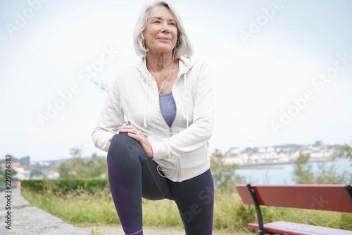 Leinwanddruck Bild  Senior woman stretching outdoors before running