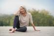 Leinwanddruck Bild -   Beautiful elderly woman sitting outdoors in sportswear