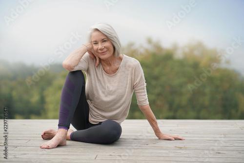 Leinwanddruck Bild   Beautiful elderly woman sitting outdoors in sportswear