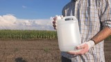 Farmer holding pesticide chemical jug in cornfield. Blank unlabeled bottle as mock up copy space for herbicide, fungicide or insecticide used in corn crop farming. - 229783158