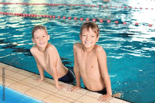 Leinwandbild Motiv Cute little boys in indoor swimming pool
