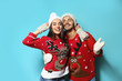 Leinwandbild Motiv Young couple in Christmas sweaters and knitted hats on color background