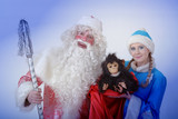 Snow maiden and Santa Claus holding gifts near the Christmas tree - 229794730
