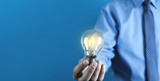 Businessman holding light bulb. Concept of new idea - 229798579
