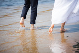 Newlyweds in wedding clothes are walking barefoot in the surf
