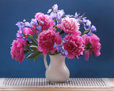 Peonies and irises. Beautiful bouquet of garden flowers in a jug.