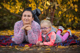 Portrait of mother and little daughter in autumnal scenery - 229816713