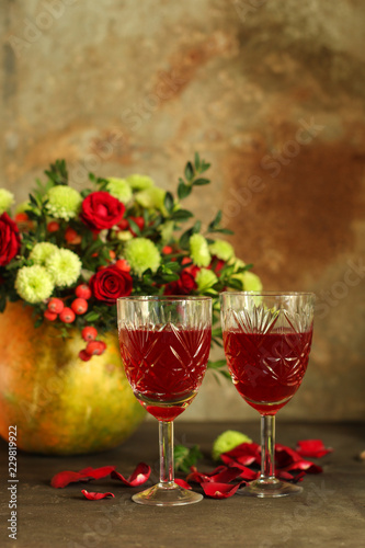 red wine in a glass and flowers on a wooden background. top view. © Alesia Berlezova