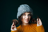Close up studio portrait of young beautiful happy smiling girl wearing stylish gray beanie hat and yellow sweater, holding her hair, braids posing on dark background. Copy, empty space for text