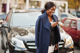 Success stylish african american woman in coat against black business suv car looking at phone. - 229866998