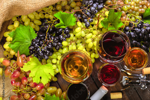 wine with branches of white grapes. On a wooden table. © fotofabrika