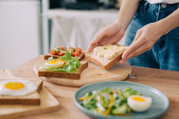 Closeup of the hands of young man preparing a sandwich at home