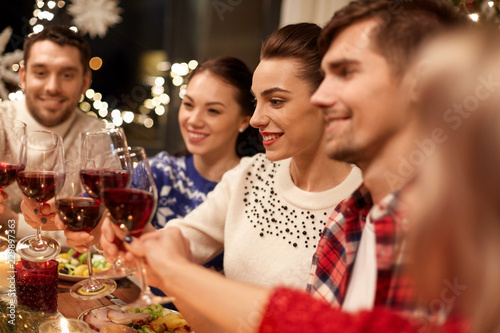 Leinwanddruck Bild holidays and celebration concept - happy friends having christmas dinner at home, drinking red wine and clinking glasses