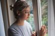 Leinwanddruck Bild - Sad woman portrait looking out the window
