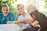 Pfleger Pflegerin spielen mit Seniorin ein Brettspiel - 229911195