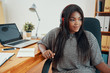 Modern African American woman in earphones sitting at table with laptop and papers in office - 229917981