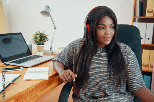 Modern African American woman in earphones sitting at table with laptop and papers in office