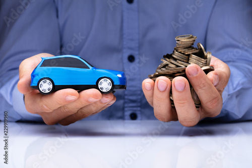Wall mural Man Holding Blue Car And Golden Coins