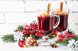 Leinwanddruck Bild - Mulled wine in glass mug with fruit and spices on white.