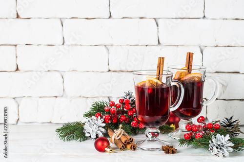 Leinwandbild Motiv Mulled wine in glass mug with fruit and spices on white.