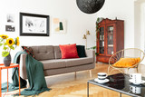 Armchair next to couch with blanket in white apartment interior with sunflowers and posters. Real photo
