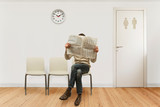 waiting room with a seated person reading newspaper - 229928599