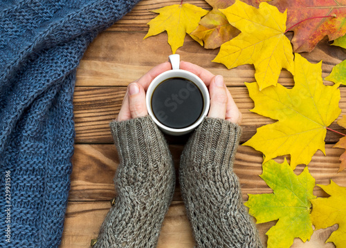 Poster Woman's hands holding hot cup of coffee on the table with autumn leaves and knitted scarf. Top view.