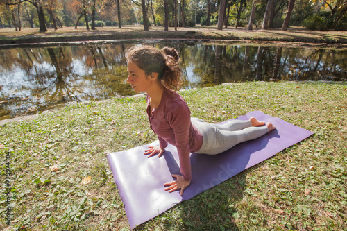 Poster Woman Practicing Yoga Exercise At City Park in The Morning