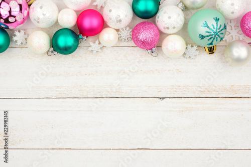 Leinwandbild Motiv Pastel Christmas bauble top border over a bright white wood background