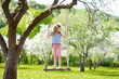 Leinwanddruck Bild - Cute little girl having fun on a swing in blossoming old apple tree garden outdoors on sunny spring day.