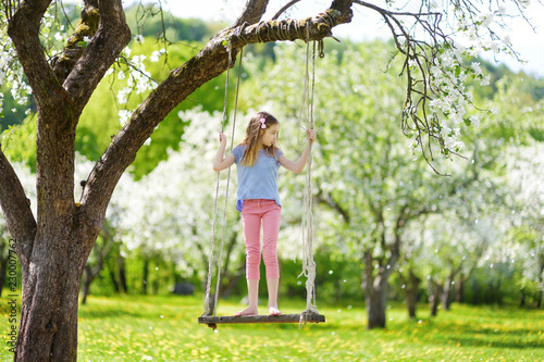 Leinwanddruck Bild Cute little girl having fun on a swing in blossoming old apple tree garden outdoors on sunny spring day.