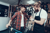 Guy and Repairman Fixes Bicycle in Sport Store
