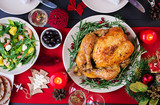 Baked turkey. Christmas dinner. The Christmas table is served with a turkey, decorated with bright tinsel and candles. Fried chicken, table.  Family dinner. Top view - 230032383