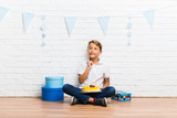 boy celebrating his birthday with a cake standing and thinking an idea - 230048550