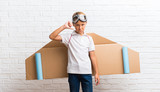 Boy playing with cardboard airplane wings on his back showing thumb down sign with negative expression - 230049301