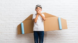 Boy playing with cardboard airplane wings on his back covering mouth with hands - 230049348